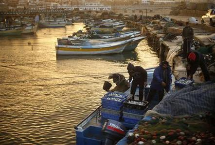 Palestinian fishermen sort boxes containing fish at Gaza Seaport in Gaza City December 13, 2012. The horizon of the claustrophobic Gaza Strip stretches further out to sea after a bloody eight-day battle last month and its main market gleams with extra supplies of locally-caught fish. In a low-key move it has yet to acknowledge, Israel moved a naval blockade it imposed in 2009 back to six miles (10 km) from the Palestinian enclave's coast from three on Nov 23, two days after signing an Egypt-brokered truce with Gaza's Hamas rulers. REUTERS/Mohammed Salem