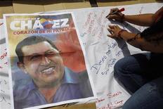 """Los venezolanos esperaban el jueves por tercer día consecutivo noticias del presidente Hugo Chávez, que según el Gobierno se encuentra """"estable"""" tras una operación para combatir el cáncer, mientras líderes de su partido pedían apoyo al vicepresidente si tiene que relevarlo. En la imagen del 12 de diciembre, un simpatizante de Chávez escribe un mensaje de apoyo en una gran pancarta en Caracas. REUTERS/Carlos García Rawlins )"""
