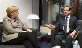 German Chancellor Angela Merkel (L) speaks with French President Francois Hollande during a meeting on the sidelines of an EU summit in Brussels December 13, 2012. European governments reached a landmark deal on Thursday that gives the European Central Bank new powers to supervise banks, boosting confidence in the single currency bloc as it enters the fourth year of its debt crisis. REUTERS/Michel Euler/Pool (BELGIUM - Tags: BUSINESS POLITICS)