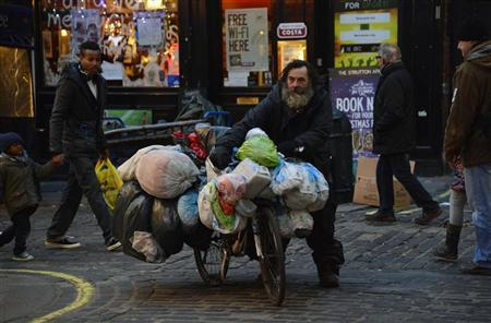 A man walks with his bike covered in bags of belongings in central London December 12, 2012. REUTERS/Toby Melville