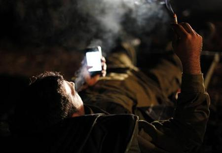 A soldier smokes a cigarette at a staging area outside the northern Gaza Strip November 21, 2012. REUTERS/Amir Cohen