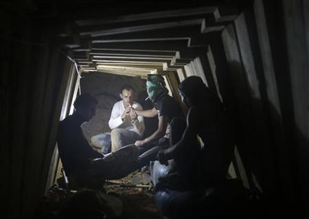 Palestinians smoke cigarettes as they work inside a smuggling tunnel dug beneath the Egyptian-Gaza border in Rafah, in the southern Gaza Strip November 26, 2012. Knee-deep in craters carved out by Israeli air strikes, Palestinians wielded shovels and planks to reopen tunnels used to smuggle in goods from Egypt to Gaza, as international aid agencies raced to replenish Gaza's supplies. REUTERS/Mohammed Salem