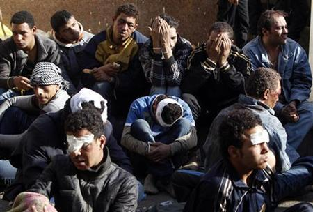 Protesters who were injured during overnight clashes between supporters and opponents of Egyptian President Mohamed Mursi, are pictured with their hands bound while being detained in front of the presidential palace in Cairo, December 6, 2012. REUTERS/Mohamed Abd El Ghany