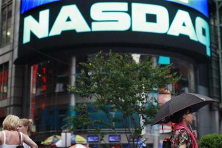 People walk outside the Nasdaq Market site in New York's Times Square, July 23, 2012. REUTERS/Brendan McDermid/Files