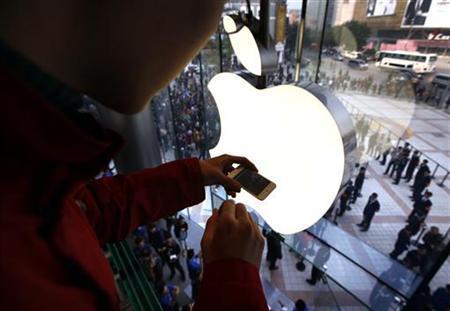 A man takes a photograph using his iPhone of members of the public entering a new Apple store during the official opening in Beijing's Wangfujing shopping district October 20, 2012. REUTERS/David Gray/Files
