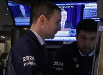"Traders work on the floor of the New York Stock Exchange while a screen shows U.S. Federal Reserve Chairman Ben Bernanke's news conference, December 12, 2012. Stocks ended little changed on Wednesday, giving up most of the day's gains after Bernanke reiterated that monetary policy won't be enough to offset damage from the ""fiscal cliff."" REUTERS/Brendan McDermid (UNITED STATES - Tags: BUSINESS POLITICS)"