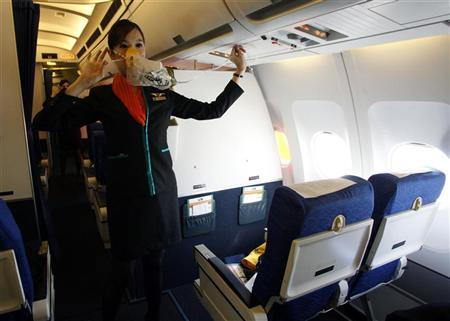PC Air flight attendant Chayathisa Nakmai, 24, demonstrates in-flight safety to passengers on P.C. Air's aircraft at Bangkok's Suvarnabhumi International Airport December 15, 2011. REUTERS/Chaiwat Subprasom