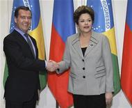 """O primeiro-ministro russo, Dmitri Medvedev (esquerda), cumprimenta a presidente brasileira, Dilma Rousseff, durante reunião em Moscou, Rússia. Dilma Rousseff disse após o encontro que não tem """"mais o que fazer"""" nas negociações políticas para o estabelecimento de uma nova divisão dos royalties do petróleo, tema que gerou embate entre Estados e municípios produtores e não produtores. REUTERS/Yekaterina Shtukina/RIA Novosti/Pool"""
