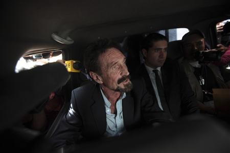 Software pioneer John McAfee is escorted by immigration officers at La Aurora International Airport in Guatemala City December 12, 2012. REUTERS/William Gularte
