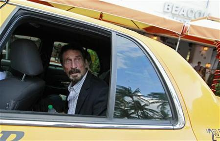 Computer software pioneer John McAfee speaks with a reporter from a taxi outside his hotel in Miami Beach, Florida December 13, 2012. REUTERS/Joe Skipper