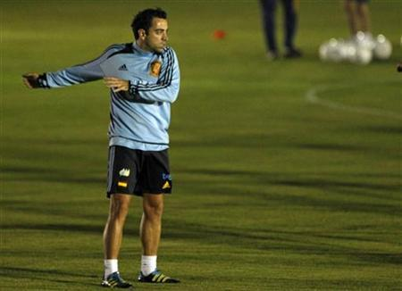 Xavi Hernandez stretches during a practice session in San Antonio de Belen November 13, 2011. REUTERS/Juan Carlos Ulate/Files