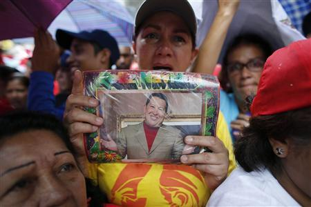 A supporter of Venezuelan President Hugo Chavez holds a picture of him while attending a campaign rally of United Socialist Party of Venezuela (PSUV)'s candidate for Miranda state governor, Elias Jaua, in Los Teques outside Caracas December 13, 2012. REUTERS/Jorge Silva