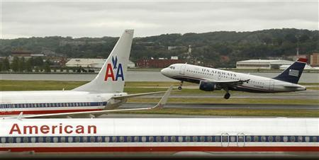 A US Airways plane takes off behind an American Airlines jet at Ronald Reagan National Airport in Washington April 23, 2012. REUTERS/Kevin Lamarque