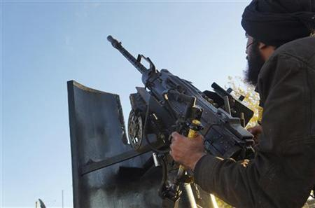 A Free Syrian Army fighter aims his weapon towards a Syrian military warplane (not pictured) in Aleppo's al-Amereya district December 12, 2012. REUTERS/Saleh Anadani