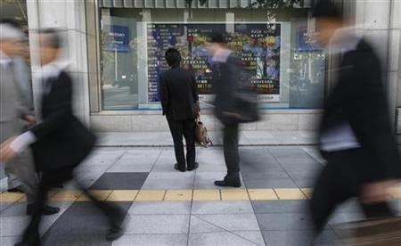A man looks at a stock quotation board outside a brokerage in Tokyo November 7, 2012. REUTERS/Toru Hanai/Files