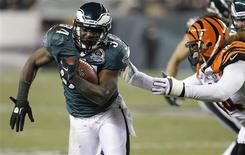Philadelphia Eagles Bryce Brown (34) avoids a tackle from the Cincinnati Bengals Domata Peko (R) during the second quarter of their NFL football game in Philadelphia, Pennsylvania, December 13, 2012. REUTERS/Tim Shaffer