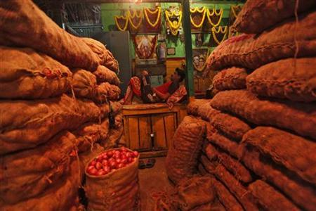 A vendor rests next to sacks of onions at a wholesale vegetable market in Kolkata March 16, 2012. REUTERS/Rupak De Chowdhuri/Files
