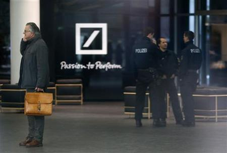 Police officers stand inside the lobby of the headquarters of Germany's largest business bank, Deutsche Bank AG in Frankfurt December 12, 2012. Deutsche Bank on Wednesday said its Frankfurt offices were being searched by prosecutors probing a tax evasion scheme involving the trading of carbon permits. The prosecutor said the probe related to severe tax evasion, money laundering and obstruction of justice, with the investigation targeting 25 employees of the bank. Deutsche Bank said it was cooperating fully with the authorities. REUTERS/Kai Pfaffenbach (GERMANY - Tags: BUSINESS CRIME LAW)