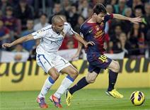 El gol en el minuto 90 de Carlos Aranda dio el jueves al Real Zaragoza una victoria por 1-0 sobre el Levante en el partido de ida de octavos de final de la Copa del Rey mientras el Real Betis no pudo pasar del empate 1-1 ante Las Palmas, de Segunda División. En la imagen, Carlos Aranda pelea por el balón con Lionel Messi (D) del Barcelona en su encuentro de Liga en el estadio Nou Camp, el pasado 17 de noviembre de 2012. REUTERS/Albert Gea