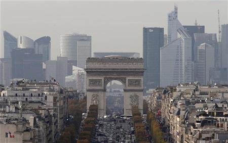 The skyline of La Defense is seen behind Paris' landmark, the Arc de Triomphe, November 20, 2012. REUTERS/Christian Hartmann