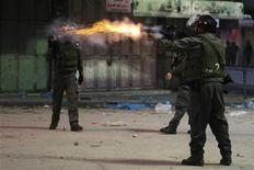 Израильский солдат зажигает баллон со слезоточивым газом во время беспорядков в Хевроне 6 декабря 2012 года. Израильские солдаты ударили двух операторов агентства Рейтер, заставили их раздеться на улице и распылили перед ними баллон со слезоточивым газом, после чего одному из них потребовалась медицинская помощь. REUTERS/Mussa Qawasma
