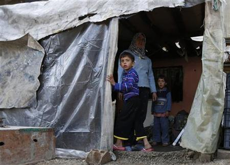 Syrian refugee Am Ahmed stands with her children at her temporary home in a garage where she lives with her family in Bar Elias village in the Bekaa valley December 13, 2012.REUTERS/ Jamal Saidi