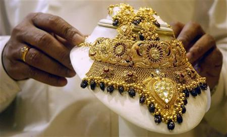 A shopkeeper displays a gold necklace at a jewellery shop in Agartala, October 18, 2007. REUTERS/Jayanta Dey/Files