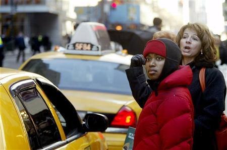 Commuters try to hail taxis near Grand Central Station in New York December 20, 2005. REUTERS/Keith Bedford
