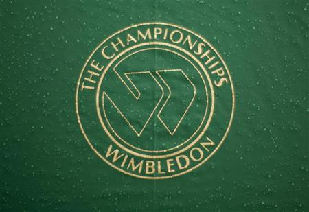 The Wimbledon logo is seen on an umbrella at centre court as rain delays the quarter-finals match between Roger Federer of Switzerland and Mario Ancic of Croatia at the Wimbledon tennis championships in London July 2, 2008. REUTERS/Kevin Lamarque