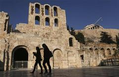 Women walk outside of the ancient Herodes Atticus theatre as the Parthenon temple is seen in the background in Athens December 13, 2012. REUTERS/John Kolesidis