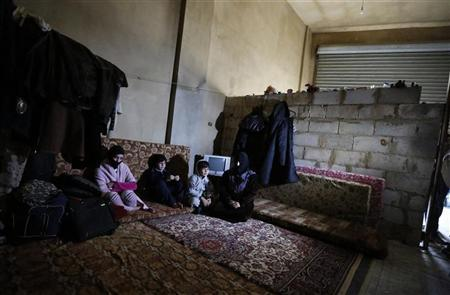 A Syrian refugee family sit inside the garage where they live in Bar Elias village in the Bekaa valley December 13, 2012. REUTERS/ Jamal Saidi