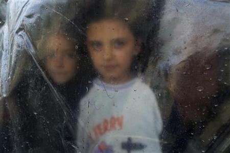 A Syrian refugee girl looks from behind a plastic sheet inside the makeshift tent where she temporarily lives with her family in Bar Elias village in the Bekaa valley December 13, 2012. REUTERS/Jamal Saidi