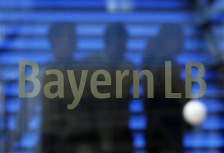 Employees of the Bavarian public sector bank BayernLB are silhouetted as they walk near the bank's logo at the BayernLB headquarters in Munich July 2, 2012. REUTERS/Michaela Rehle (GERMANY - Tags: BUSINESS POLITICS)