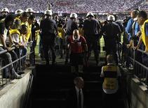 En cuanto el árbitro da el pitido final le rodean la policía antidisturbios en el campo para evitar que jugadores, entrenadores e incluso periodistas se acerquen lo suficiente para hacerle preguntas o cuestionar su actuación. Es una imagen recurrente en el fútbol brasileño y los antidisturbios siempre están presentes en los estadios, como la violencia que protagonizó el partido del miércoles por la noche, la final de la Copa Sudamericana en Sao Paulo, una de las ciudades que albergará el Mundial de 2014. En la imagen, un árbitro entra en el vestuario para hablar con los jugadores del Tigre argentino que se negaron a salir en la segunda parte tras alegar haber sido amenazados por la policía, el 12 de diciembre de 2012 en Sao Paulo. REUTERS/Nacho Doce