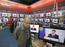 Покупатель проходит мимо телевизоров, показывающих выступление президента России Дмитрия Медведева, в магазине бытовой техники во Владикавказе 12 ноября 2009 года. Два из трех принадлежащих медиагруппе СТС Медиа российских телеканала получат доступ к цифровому вещанию в 2014-2017 годах, вероятность перехода на которое уже обошлась компании в десятки миллионов долларов, следует из сообщения СТС в пятницу. REUTERS/Kazbek Basayev