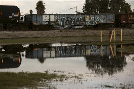 A freight train is reflected in standing water near vacant industrial land and salt marshes in Newark, California, December 13, 2012. REUTERS/Robert Galbraith