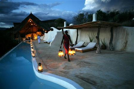A Maasai waiter brings lanterns to be placed around the swimming pool at little Shompole, a luxury eco-tourism lodge situated at some 180 km (110 miles) south of Nairobi, near the border with Tanzania, October 24, 2007. REUTERS/Radu Sigheti