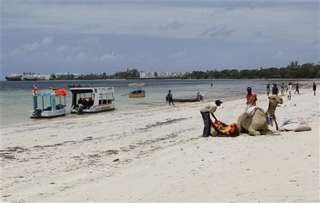 Tour operators are seen beside a camel in the deserted Bamburi public beach near the Indian Ocean in the Kenyan coastal city of Mombasa, August 30, 2012. REUTERS/Thomas Mukoya