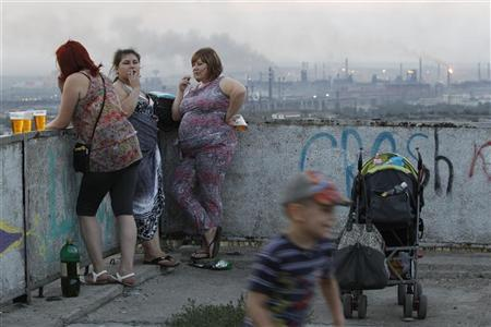 Local residents meet during sunset, with the Metallurgical Plant seen in the background, in the Southern Urals city of Magnitogorsk, July 13, 2012. REUTERS/Sergei Karpukhin