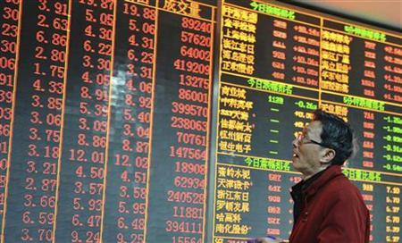 An investor looks at an electronic board showing stock information at a brokerage house in Hangzhou, Zhejiang province December 14, 2012. Chinese shares surged more than 4 percent on Friday as investors have high expectations for an annual economic conference that will set the tone for China's economic policies in 2013, Xinhua News Agency reported. REUTERS/China Daily (CHINA - Tags: BUSINESS) CHINA OUT. NO COMMERCIAL OR EDITORIAL SALES IN CHINA