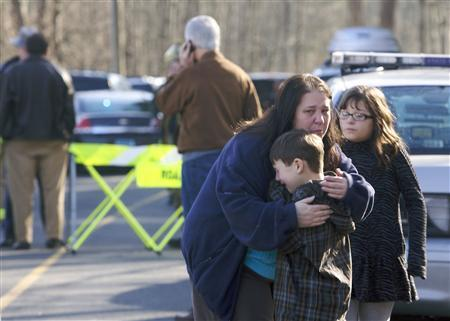 A young boy is comforted outside Sandy Hook Elementary School after a shooting in Newtown, Connecticut, December 14, 2012.REUTERS/Michelle McLoughlin