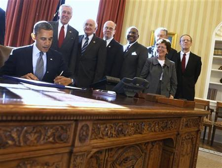 U.S. President Barack Obama (seated) signs H.R. 6156, the Russia and Moldova Jackson-Vanik Repeal and Magnitsky Rule of Law Accountability Act, in the Oval Office of the White House in Washington, December 14, 2012. From L-R are: Obama, U.S. Rep. Steny Hoyer, U.S. Rep. Sandy Levin, U.S. Rep. Jim McGovern, U.S. Rep. Gregory Meeks, acting Secretary of Commerce Rebecca Blank, CEO of Caterpillar Douglas Oberhelman (back), and President of the National Endowment for Democracy Carl Gershman. REUTERS/Larry Downing (UNITED STATES - Tags: POLITICS BUSINESS)