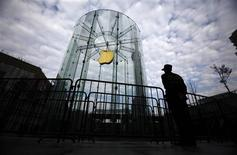 A security guard stands next to an Apple retail store during the release of the iPhone 5 in Shanghai December 14, 2012. The China release of its iPhone 5 on Friday should win Apple Inc. some respite from a recent slide in its share of what is likely already the world's biggest smartphone market, but its longer-term hopes may depend on new technology being tested by China's top telecoms carrier. REUTERS/Carlos Barria