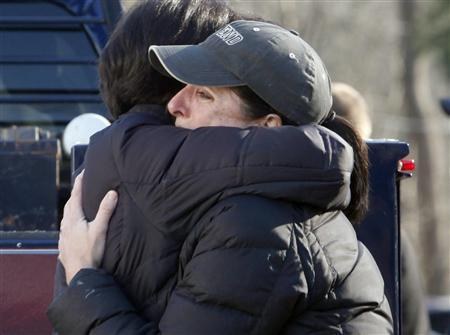 Relatives embrace each other outside Sandy Hook Elementary School following a shooting in Newtown, Connecticut, December 14, 2012. REUTERS/Michelle McLoughlin