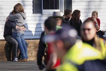 A couple embrace each other near Sandy Hook Elementary School, were a gunman opened fire on school children and staff in Newtown, Connecticut on December 14, 2012. REUTERS/Adrees Latif