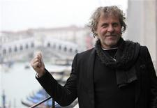 Founder of Diesel clothing company Renzo Rosso gestures as he poses in front of Rialto Bridge in Venice December 14, 2012. Public works officials in Venice said on Thursday that restoration of the Rialto Bridge that crosses the city's Grand Canal will be carried out by Otb, a company headed by Rosso, according to ANSA. REUTERS/Manuel Silvestri
