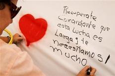 Apoiador escreve mensagem de apoio ao presidente venezuelano, Hugo Chávez, em Caracas. Uma eleição para os governos estaduais no domingo na Venezuela irá definir se a oposição permanece unida em torno do jovial líder Henrique Capriles, em meio a sinais de que Chávez pode ter de deixar o poder por motivo de saúde. 14/12/2012 REUTERS/Carlos Garcia Rawlins