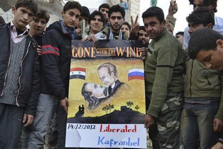 Demonstrators hold a placard during a protest against Syria's President Bashar al-Assad, after Friday prayers in Kafranbel near Idlib December 14, 2012. REUTERS/Raed Al-Fares/Shaam News Network/Handout