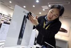 Una empleada limpia un anuncio en una concesionaria de Apple antes del lanzamiento del teléfono móvil iPhone 5 en Wuhan, China, dic 13 2012. El debut el viernes del iPhone 5 en China debería darle a Apple Inc algo de aire tras perder recientemente participación en el mayor mercado de telefonía del mundo. REUTERS/Stringer