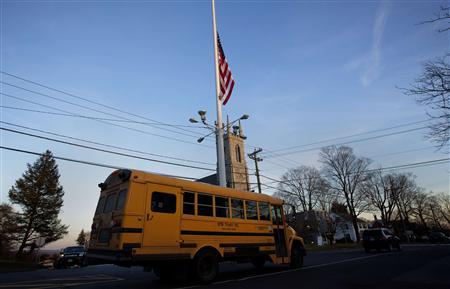 A flag is seen at half staff as a school bus passes along Main Street in Newtown, Connecticut December 14, 2012. REUTERS/Shannon Stapleton